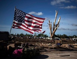 A flag is placed in the foundation of a flattened home day after a tornado devastated the town Moore, Oklahoma